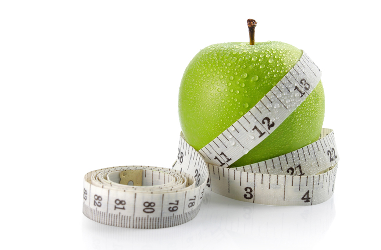 fresh apple with measuring tape. isolated over white background